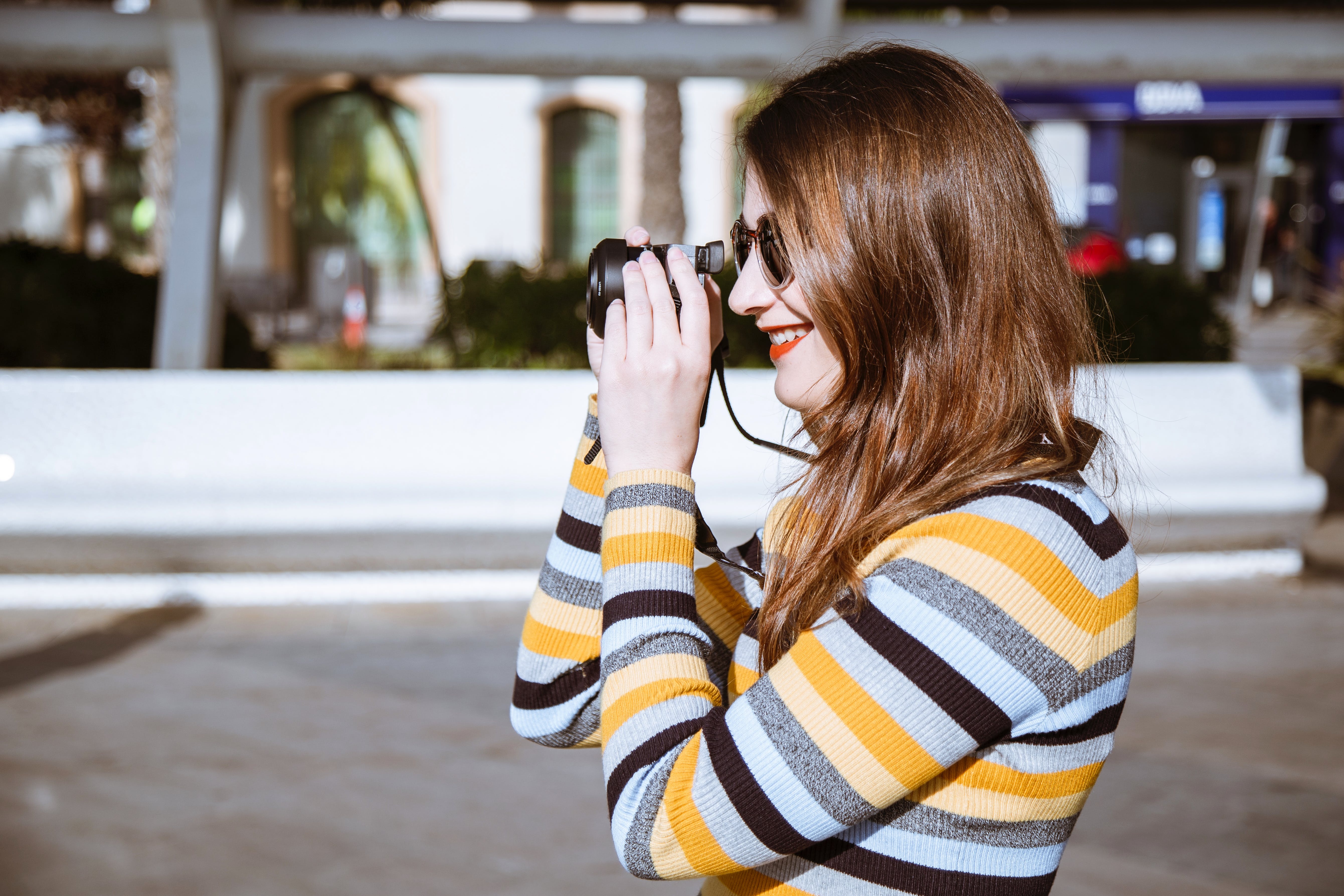 Smiling Woman Taking S Hot With Camera Beside White Building