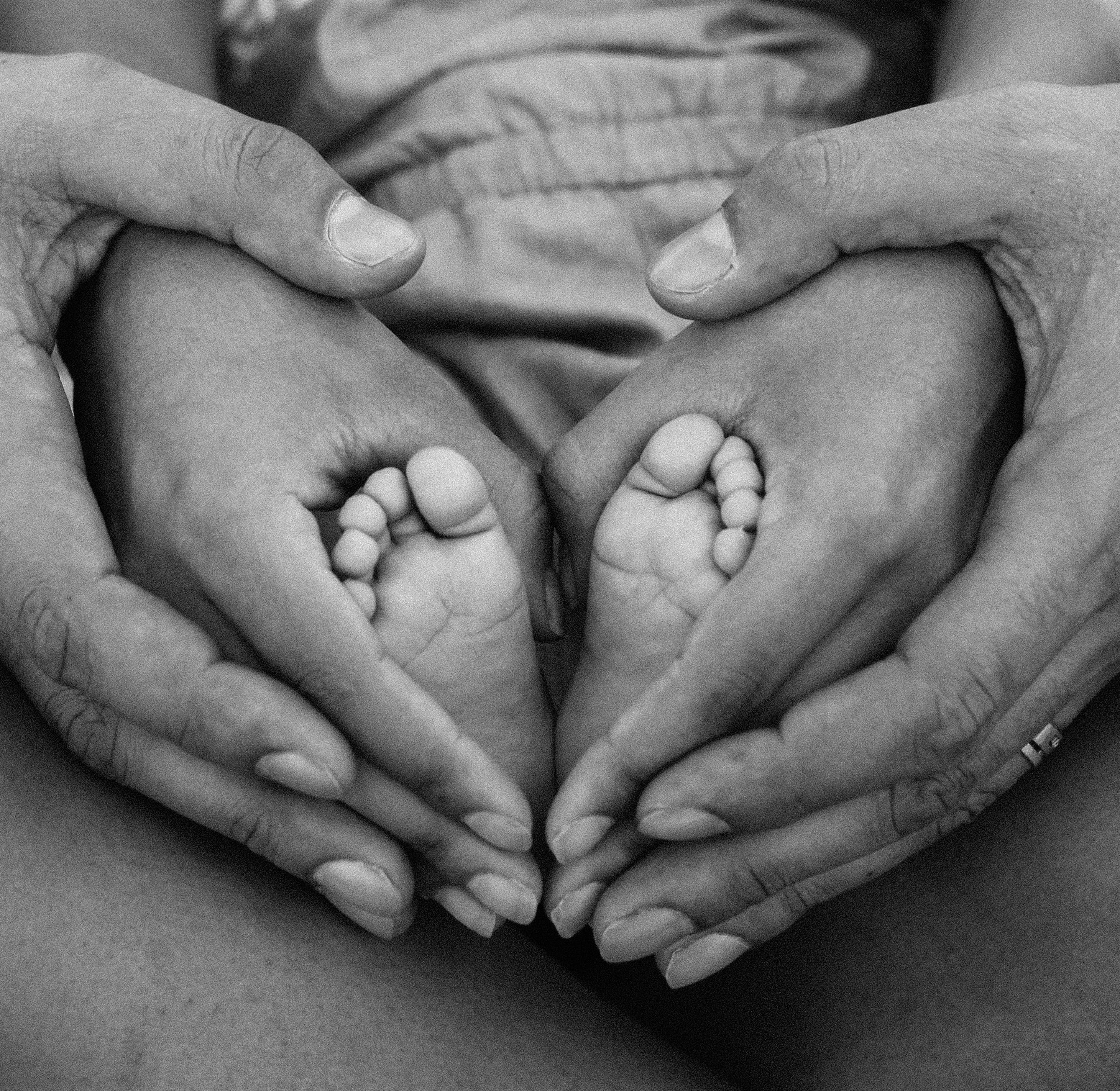 Grayscale Photo of Person Holding Feet and Hands