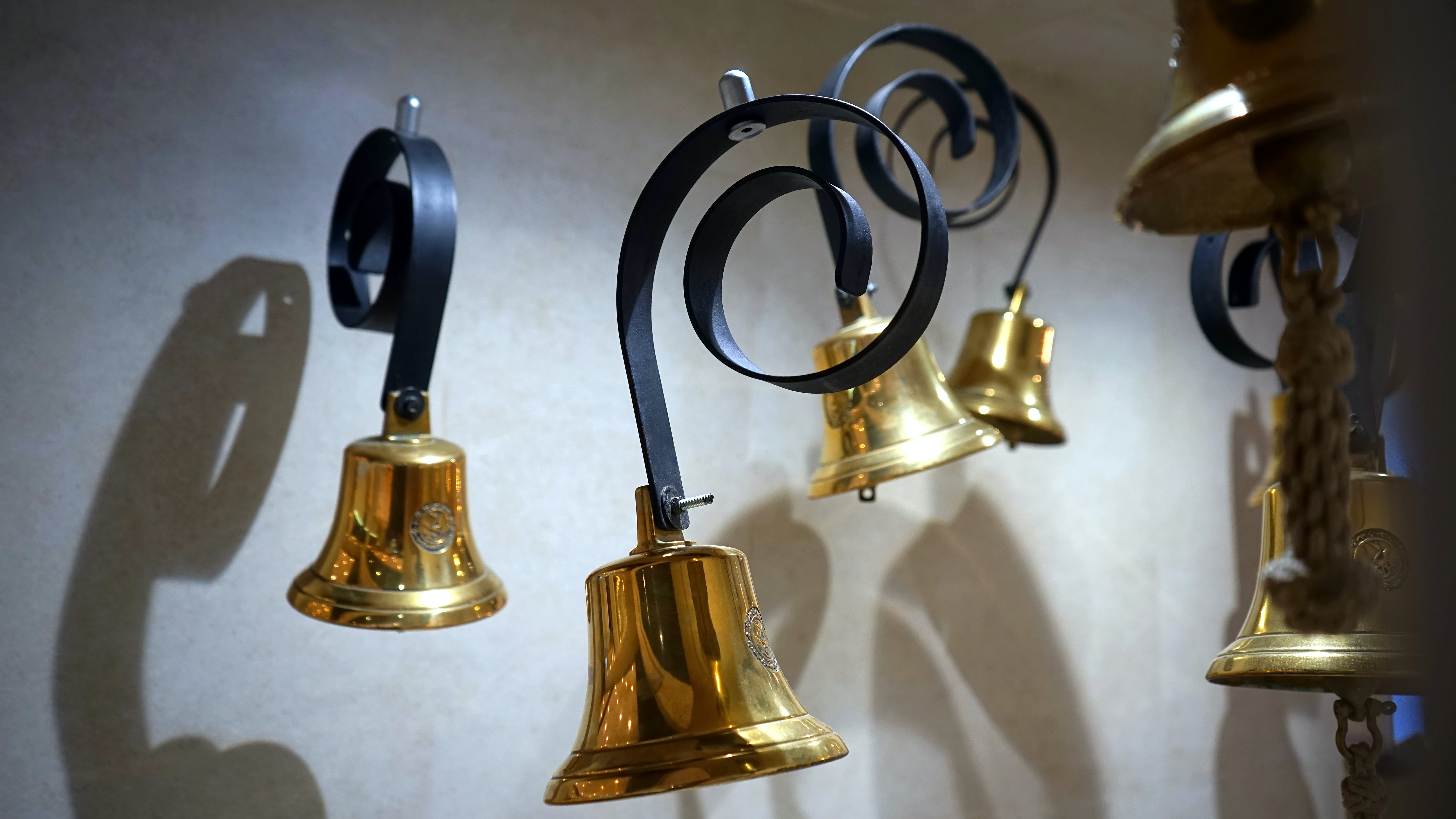 Gold-colored and Black Hanging Bells Near Wall