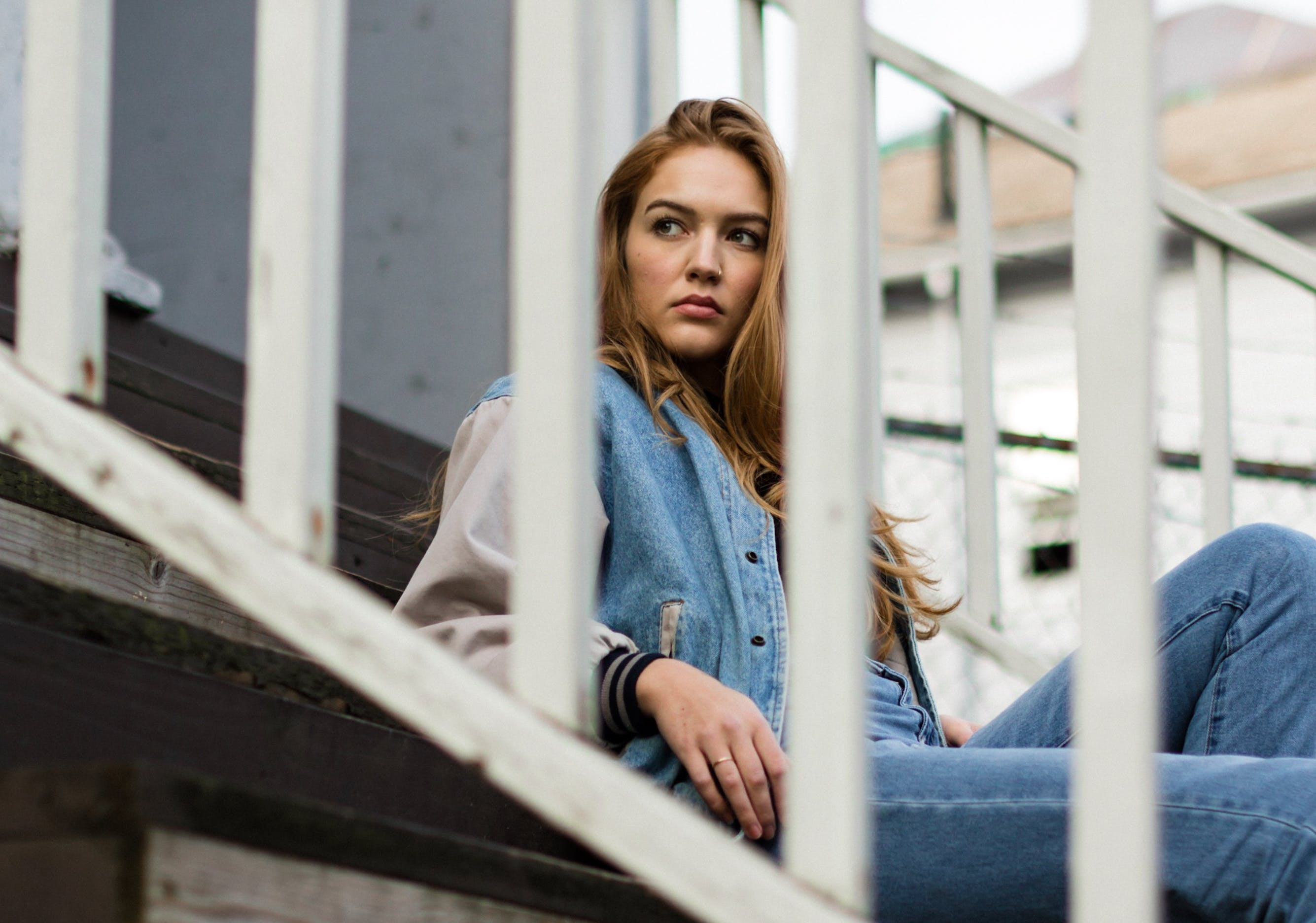 Woman Wearing Blue Denim Jacket and Blue Denim Jeans Sitting on Staircase