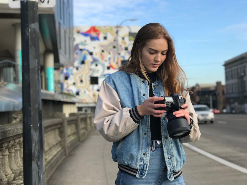 Woman Wearing Denim Jacket Holding Black Dslr Camera