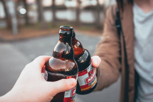 Shallow Focus Photo of Person Holding Beer Bottle