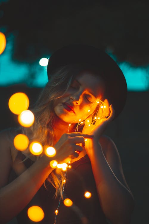 Woman Holding Yellow String Lights