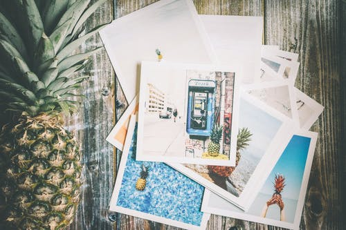 Assorted Photo Beside Pineapple on Top of Brown Surface