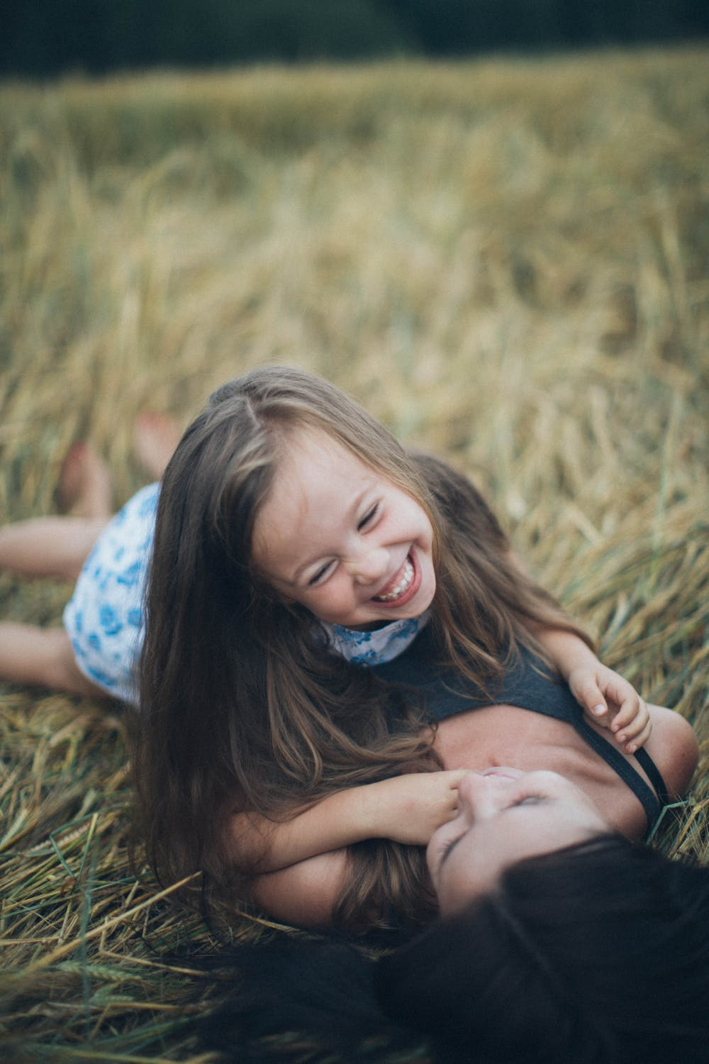 Mother and daughter lying on the lawn | Photo: Pexels