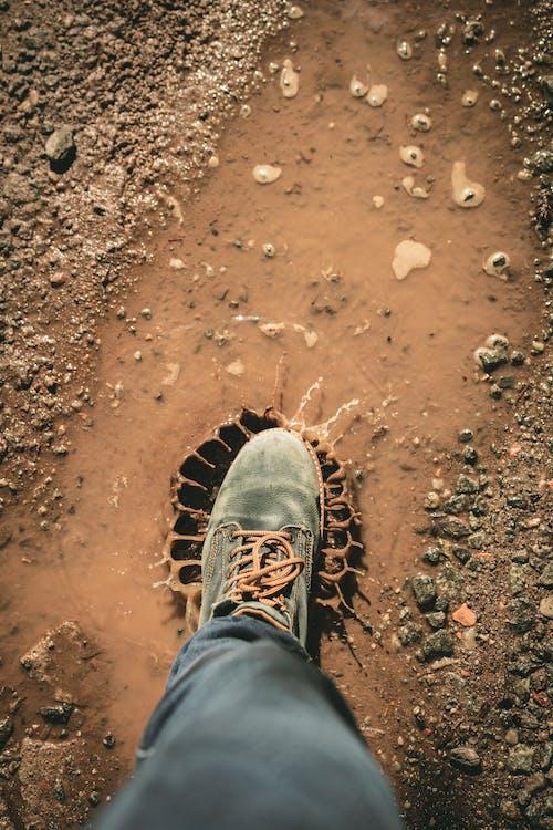 Man Wearing Gray Shoe Standing on Brown Soil