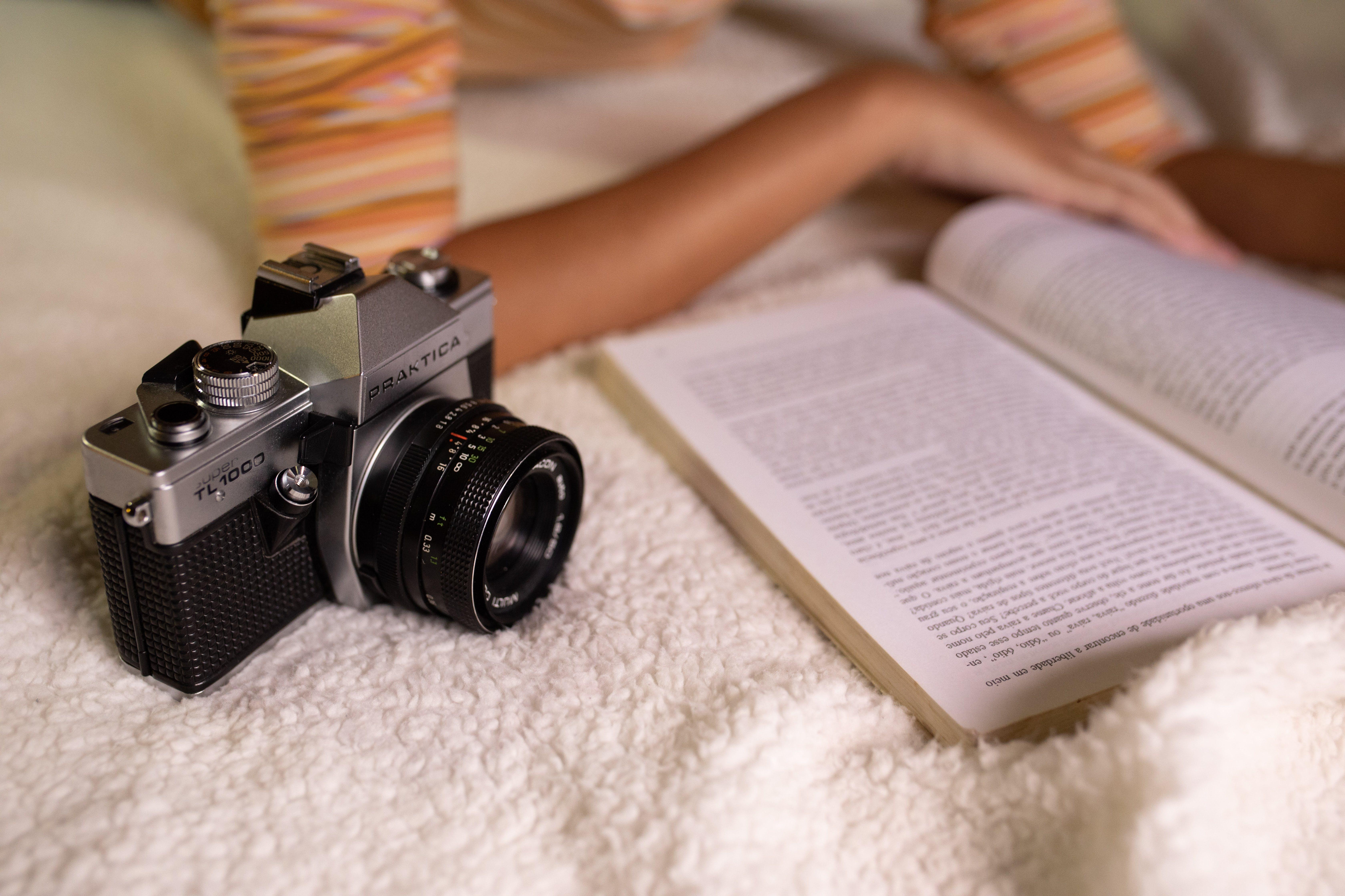Black Slr Camera Beside Open Book