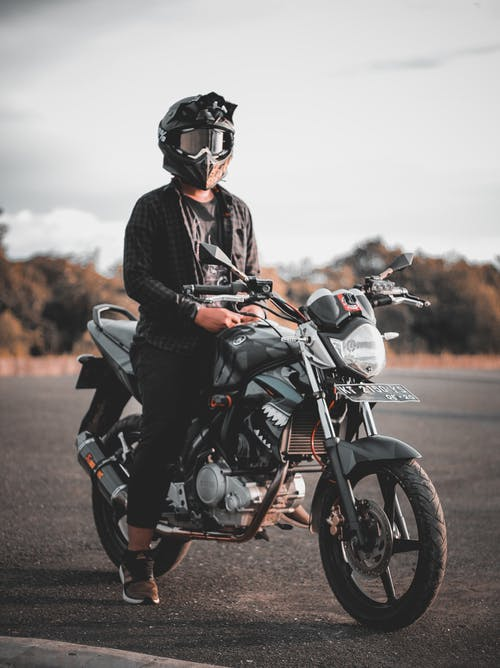 Man Riding Gray Backbone Motorcycle