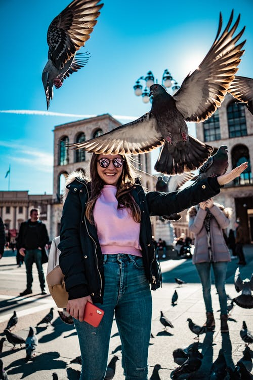 Woman Smiles and Stands Near Flying Pigeons