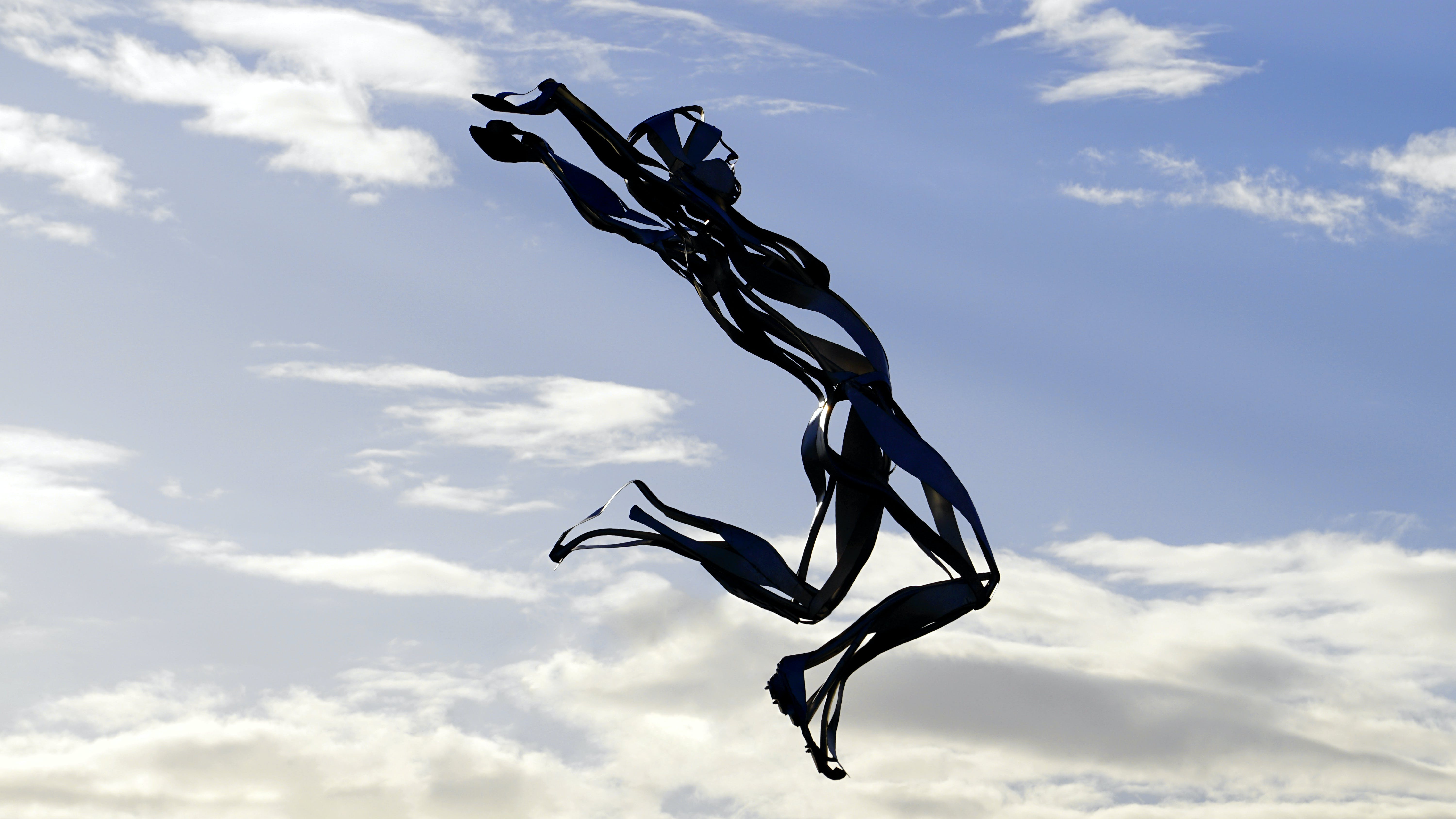 Black and Clear Human Form With Blue Sky and White Clouds Background