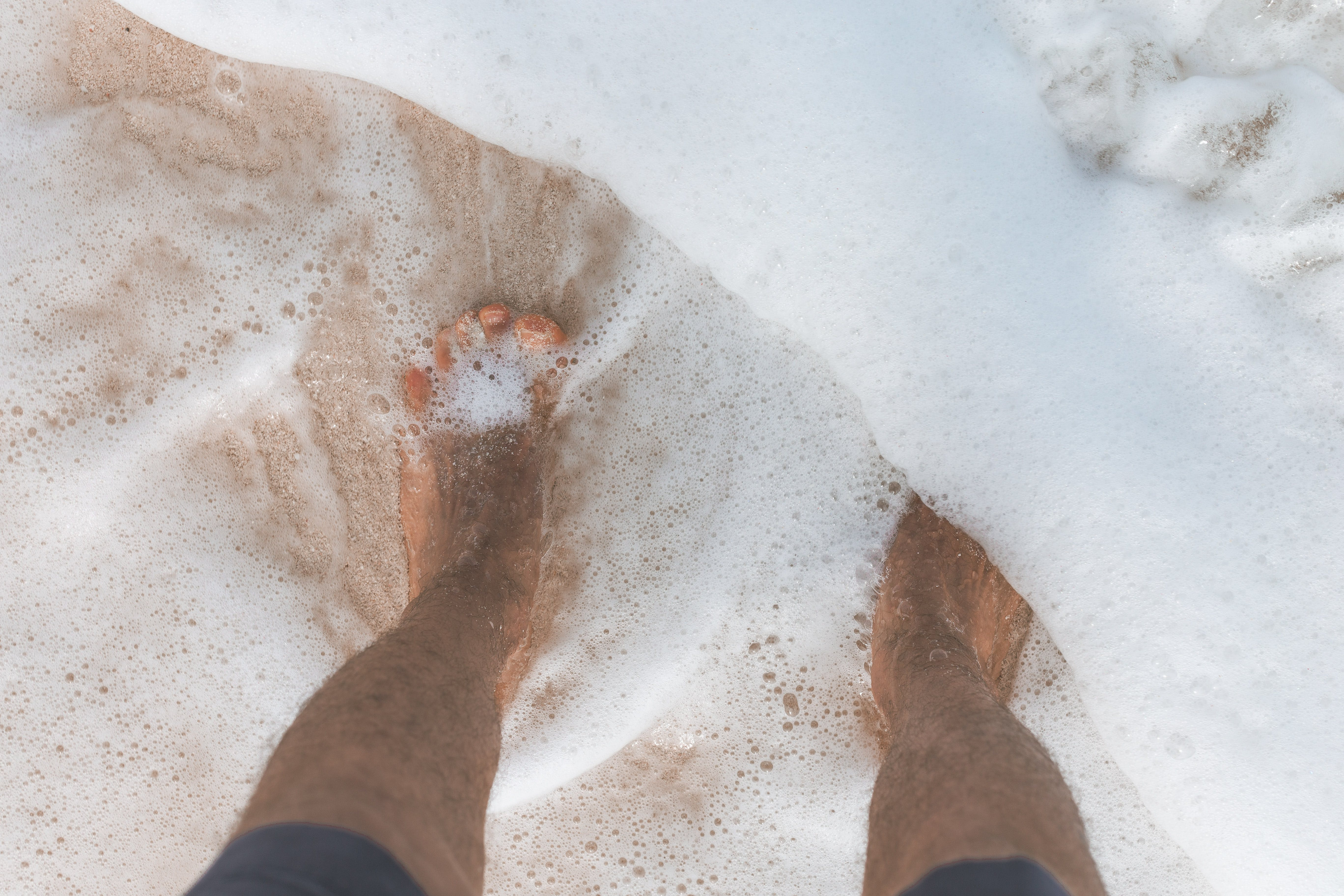 Ocean Water Washing over Man's feet