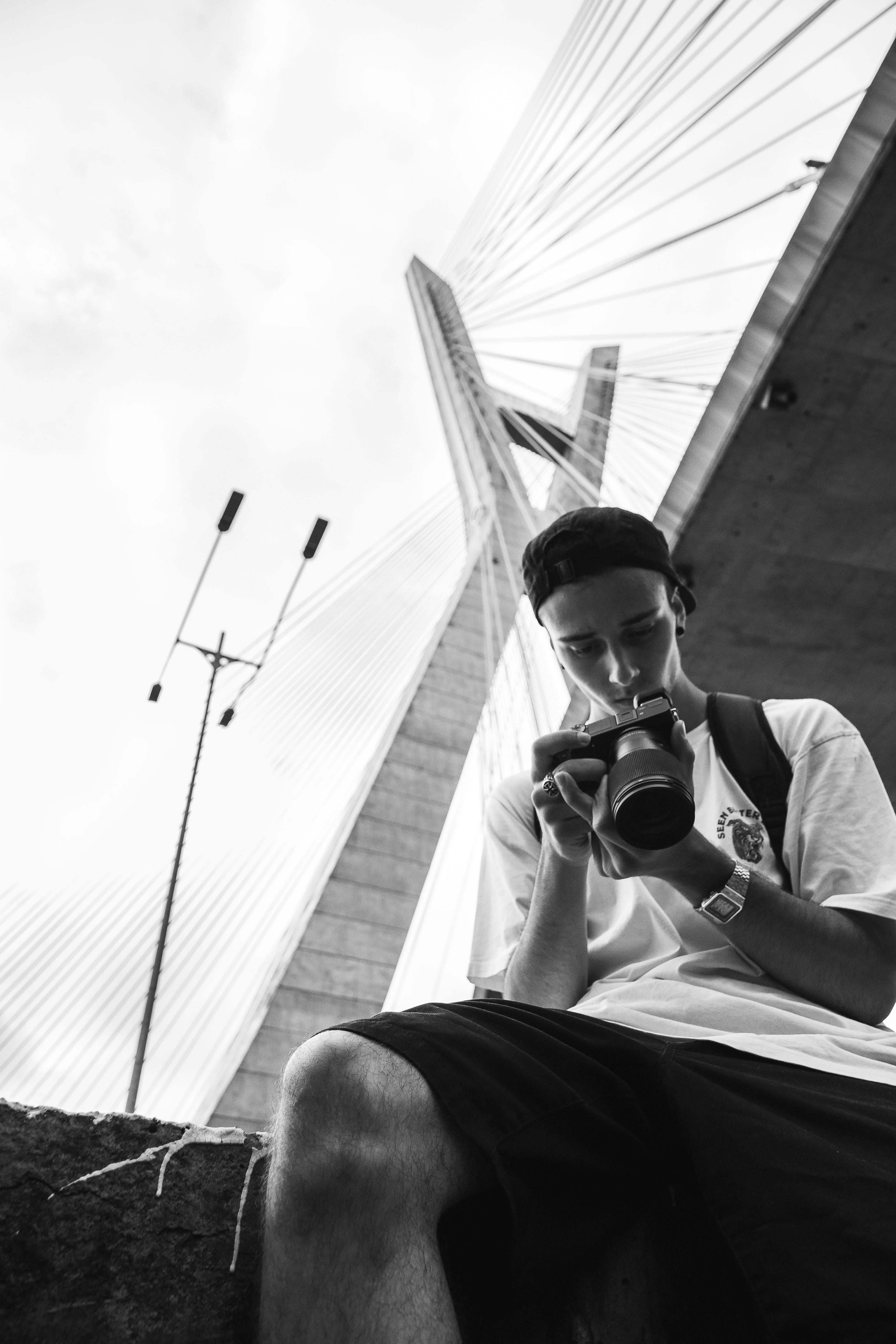Man Looking at His Camera Under the Bridge