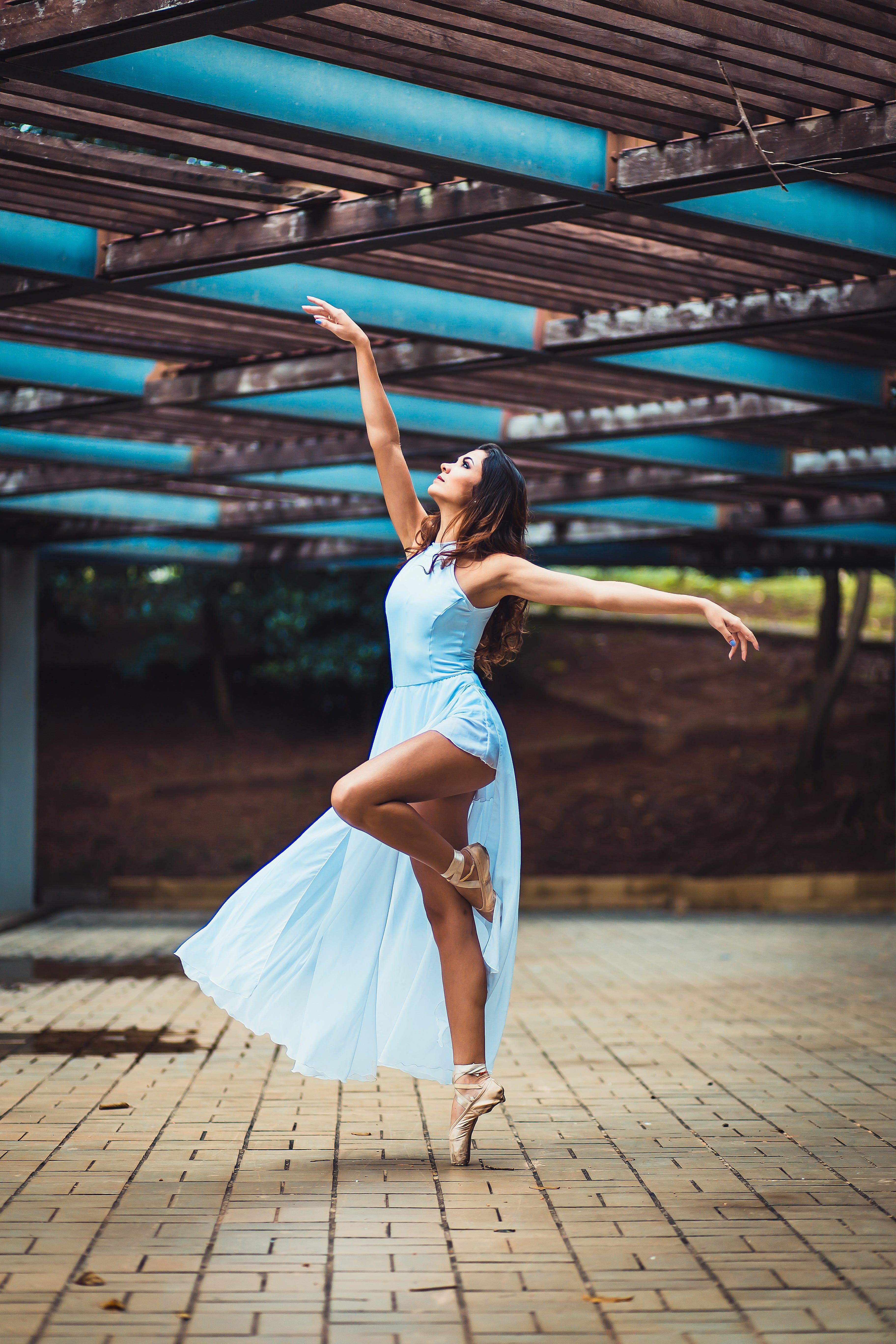 Woman Standing While Wearing Blue Sleeveless Dress