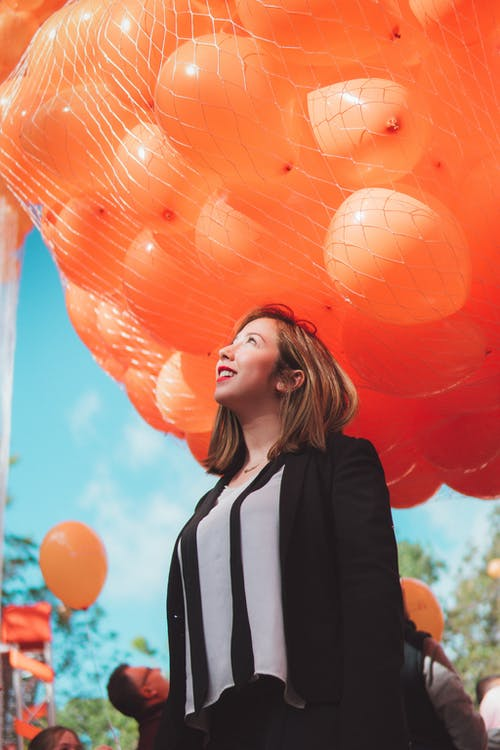 Woman in Black Cardigan Smiling Under Orange Balloons