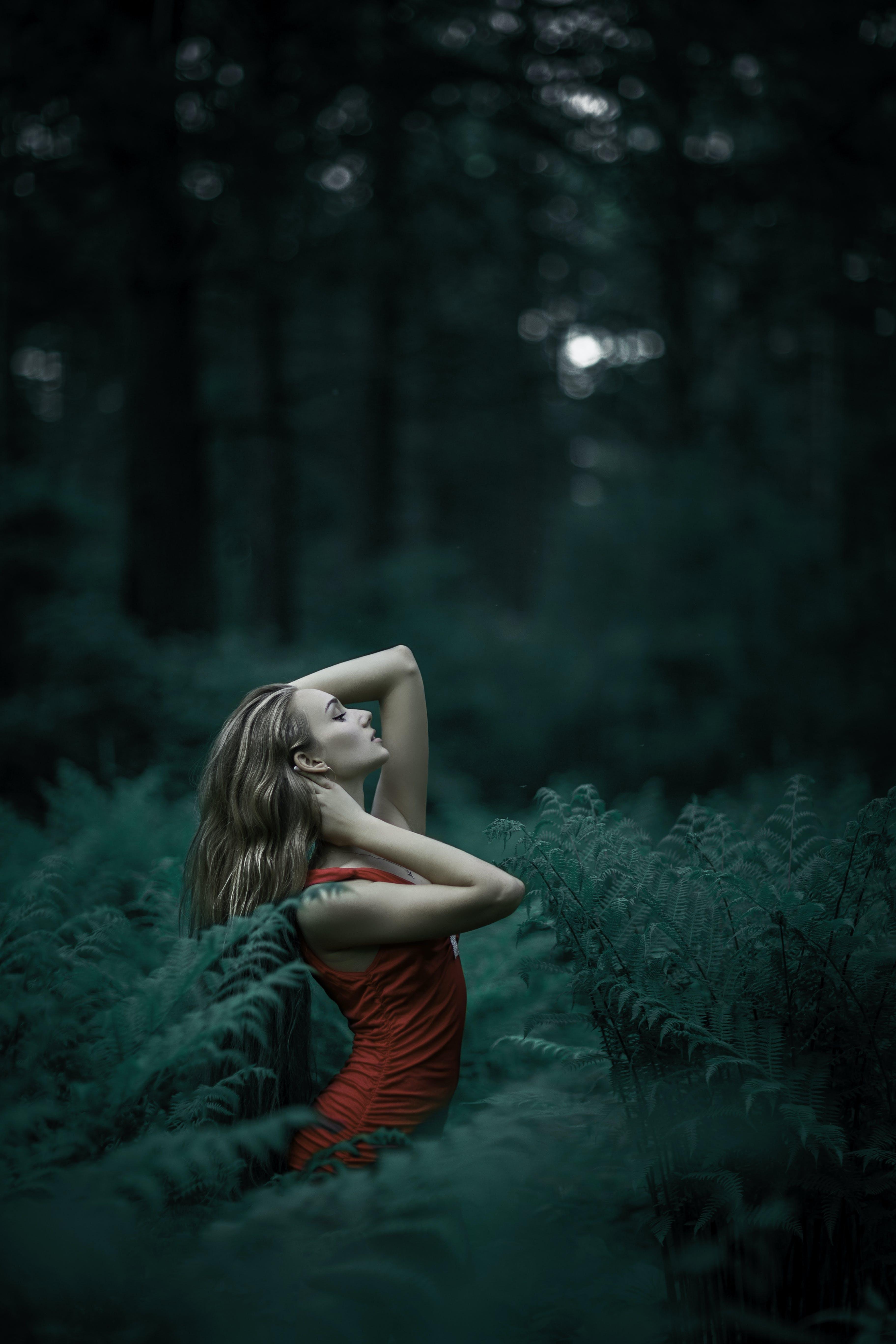 Woman Wearing Red Sleeveless Dress Standing Near Fern Leaves