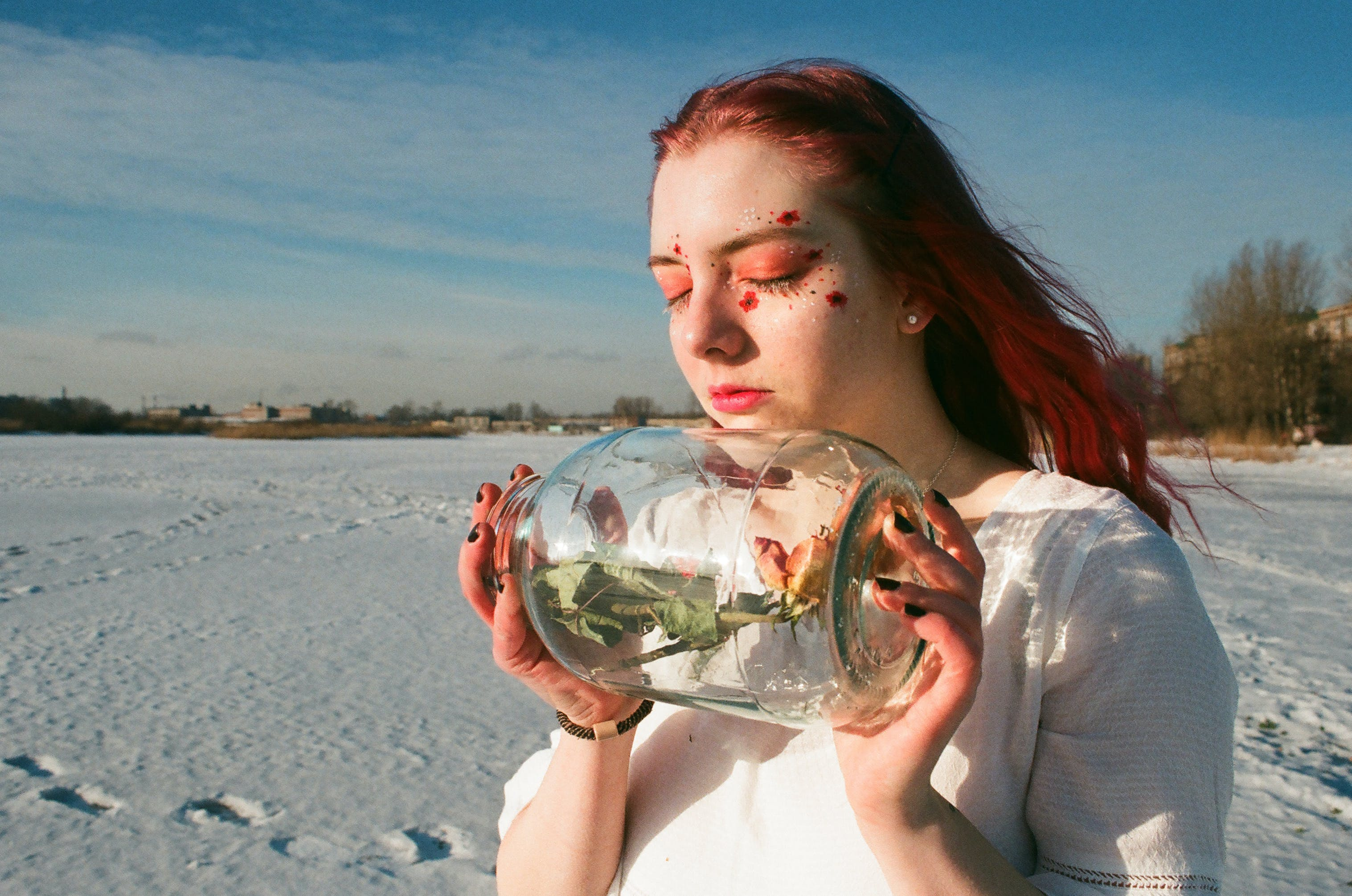 Woman Holding Clear Glass Bottle With Rose Inside