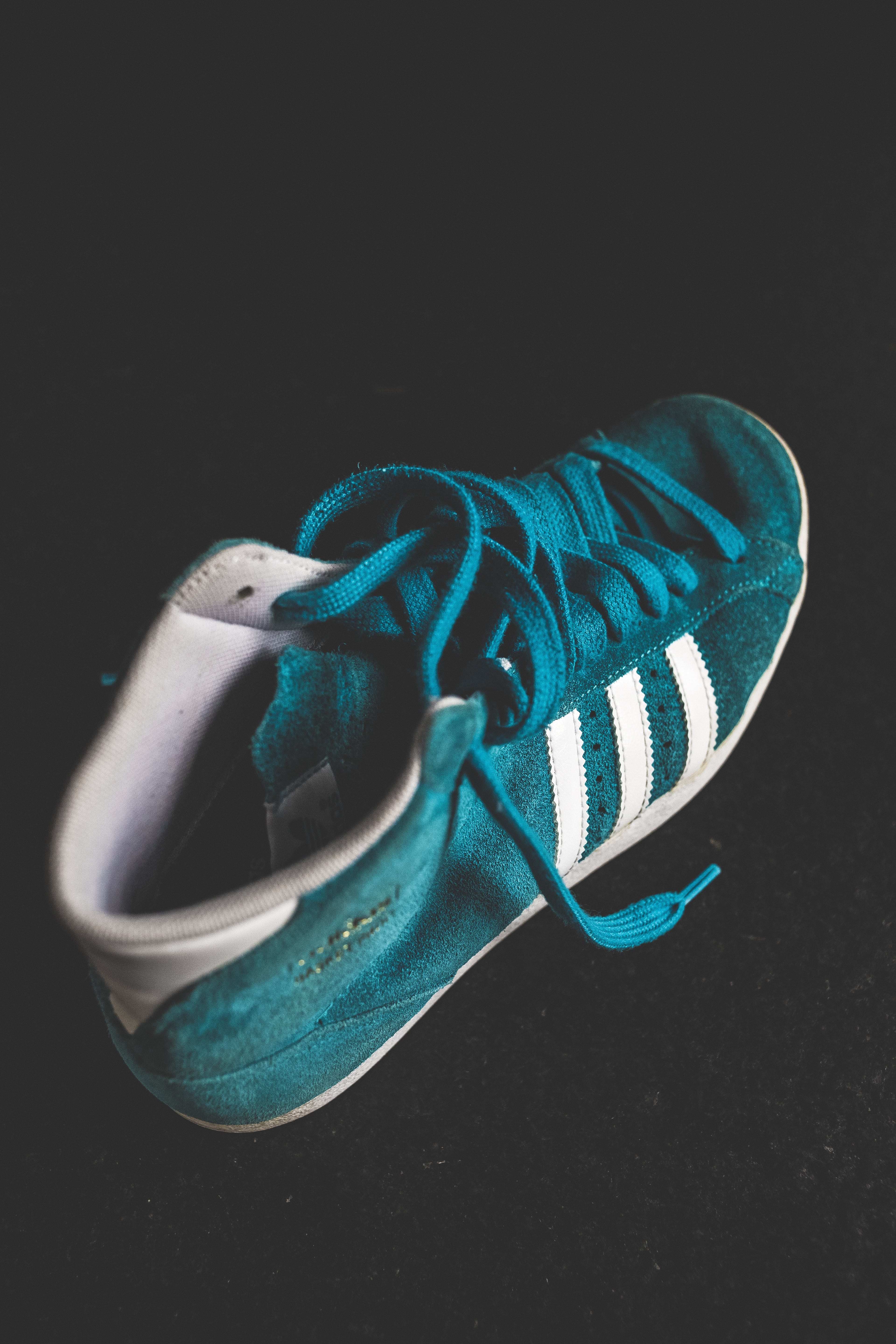 Close-up Photo of a Suede Turquoise and White Adidas High-top Sneaker