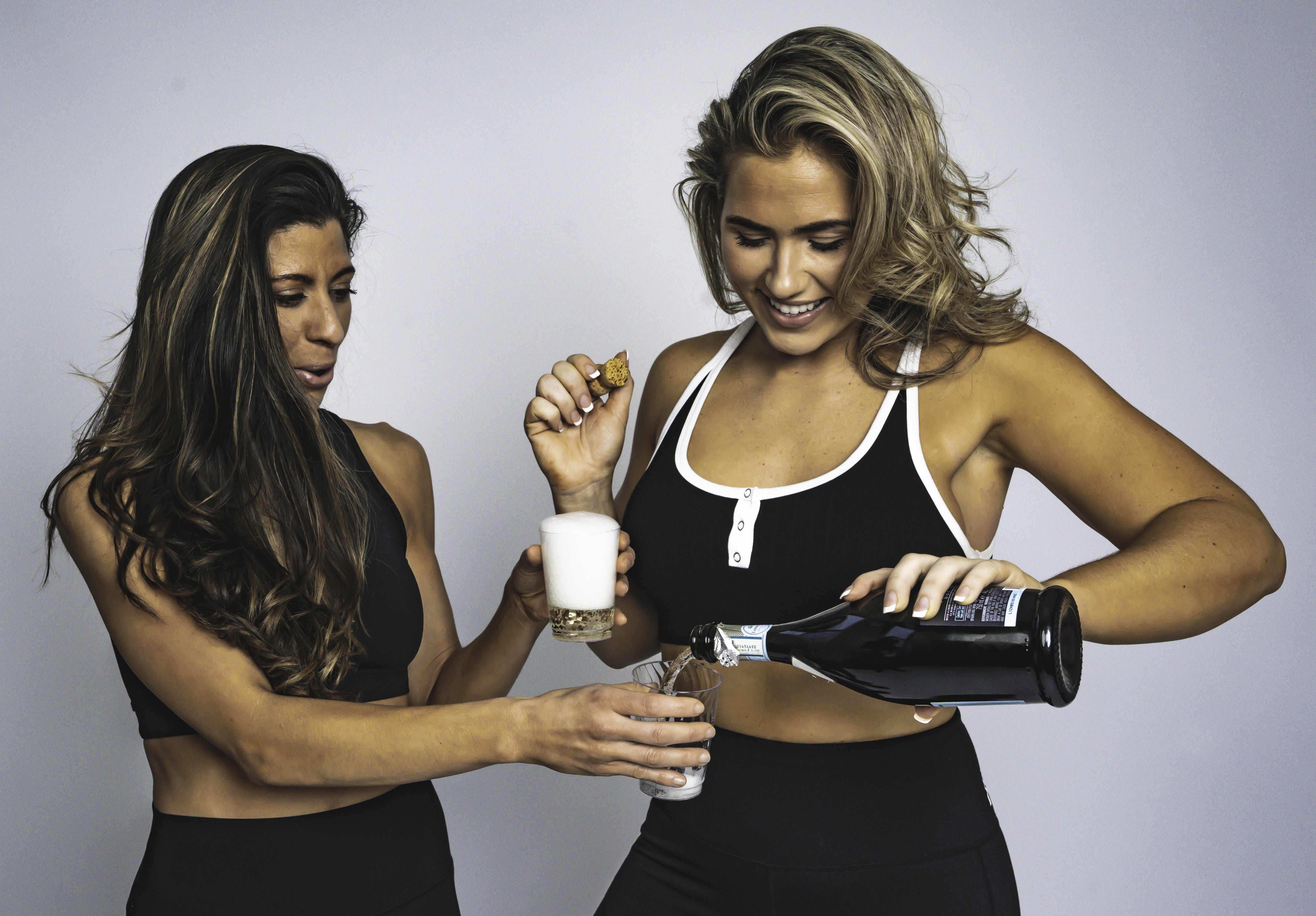 Woman Pouring Liquor On Other Woman's Glass