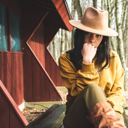 Woman in Yellow Sweater and Brown Panama Hat Sitting on Brown Wooden Table