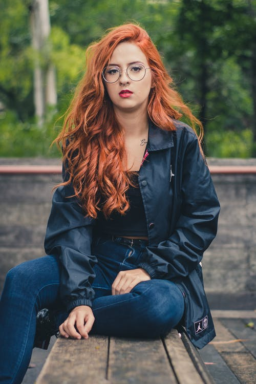 Woman in Black Leather Button-up Jacket, Blue Denim Jeans and Eyeglasses Sitting on Brown Wooden Table