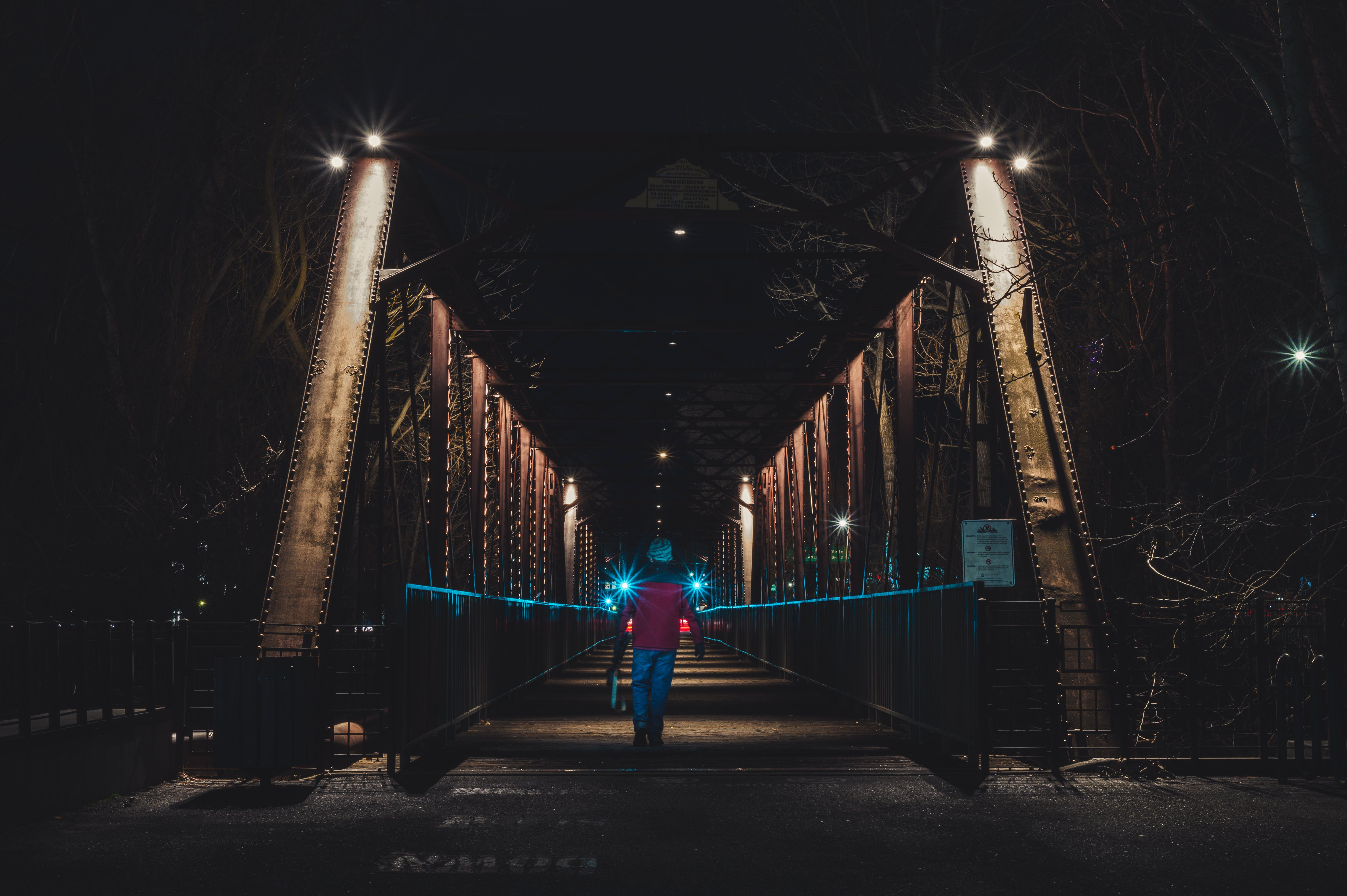 Person Walking in Bridge during Nighttime