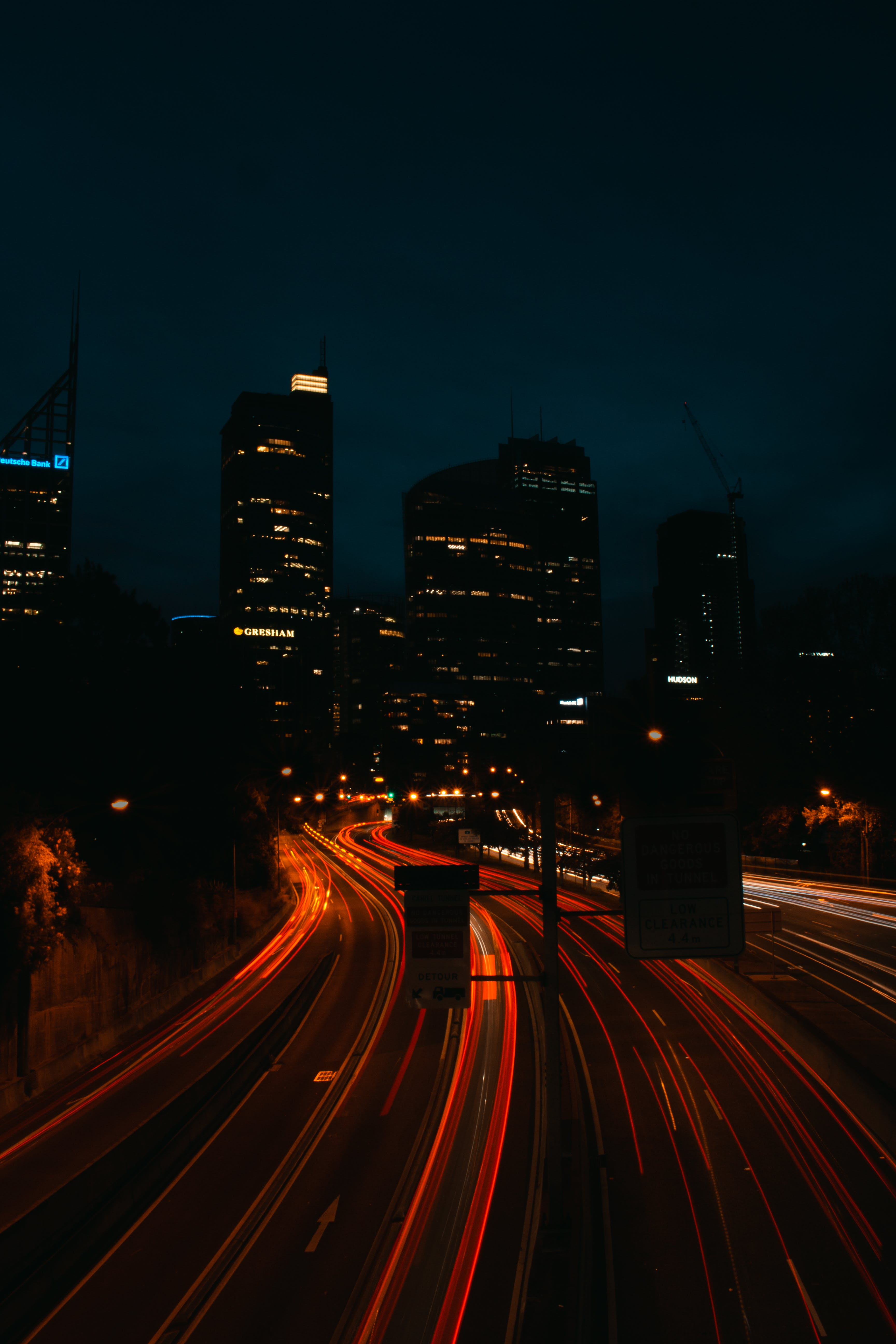 Time Lapse Photo of Lighted Highway at Night With Buildings in Background