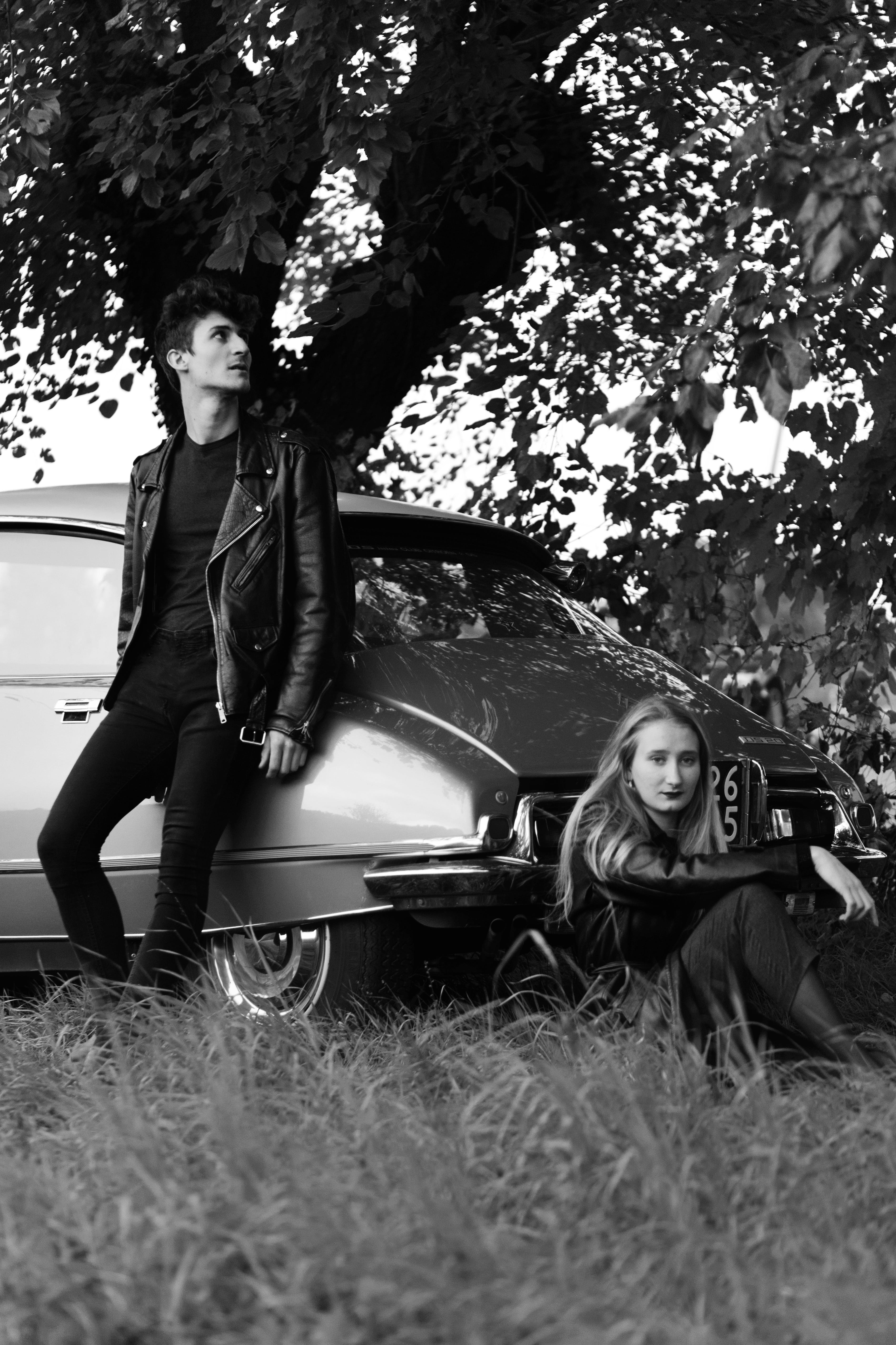 Man and Woman Leaning on Classic Car Park Near Tree