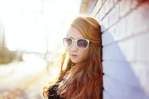 Woman Wearing White Sunglasses Leaning on Wall on Focus Photo