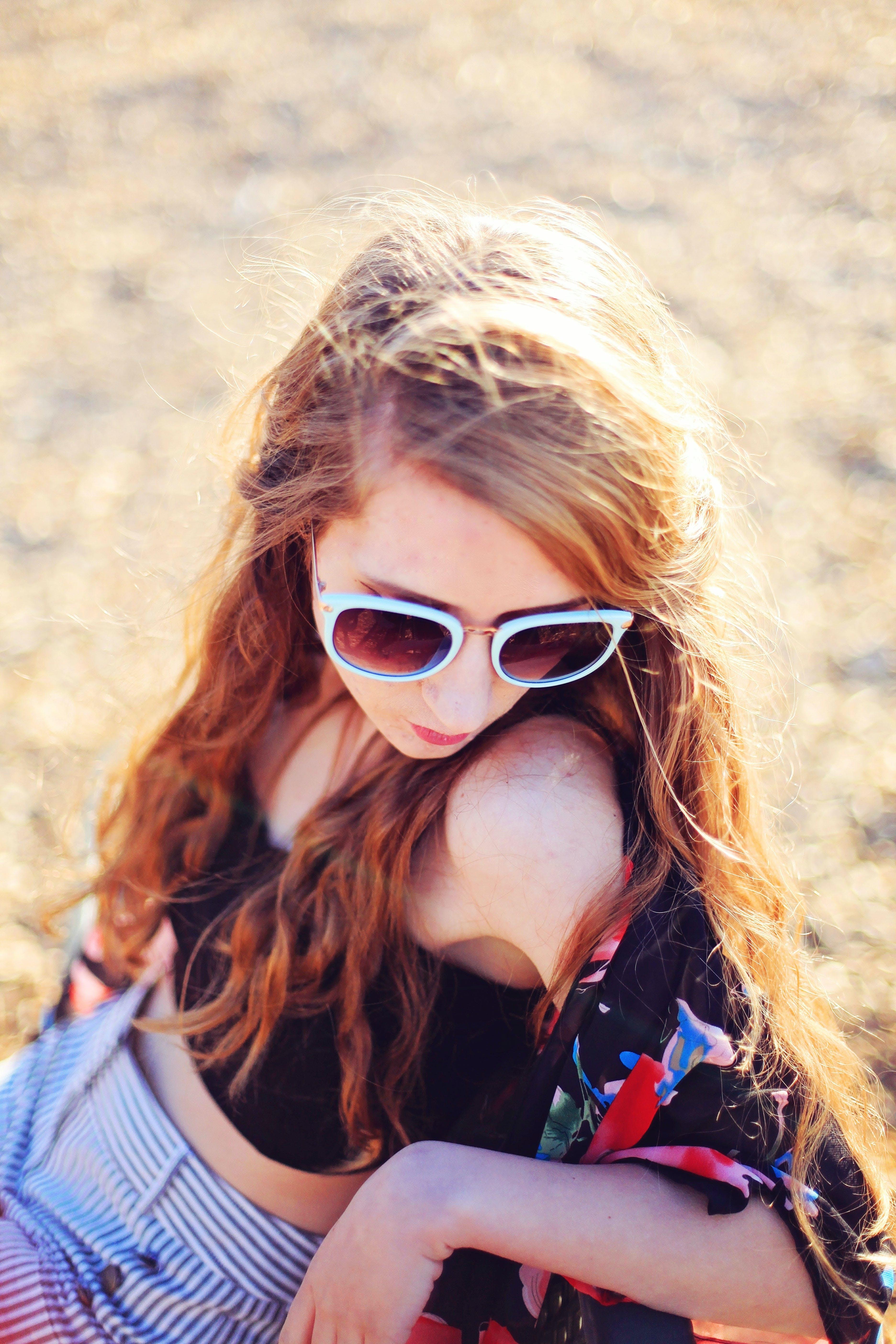 Woman Sitting on Sand Wearing White Sunglasses