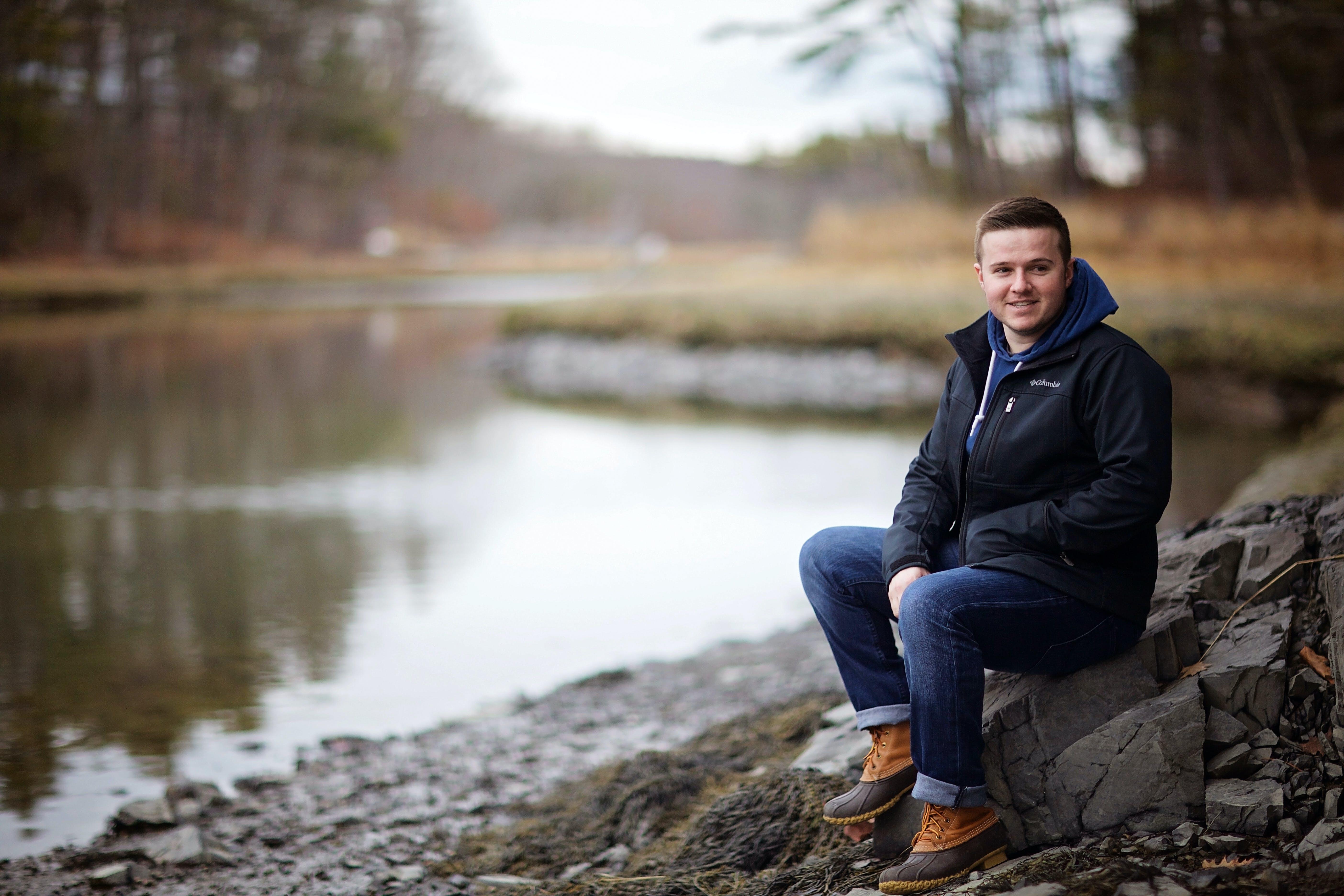 Man Wearing Black Jacket Sitting on Gray Stone Near River