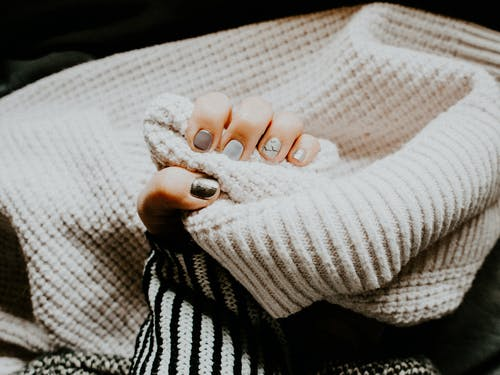 Person Holding Coat With Manicured Nails