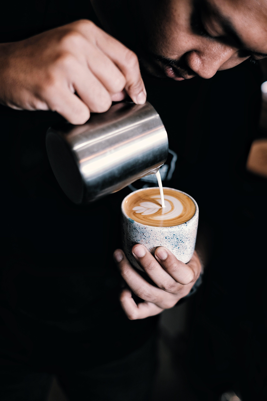 Man Pouring Coffee on Ceramic Mug