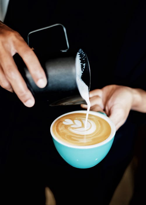 Person Pouring Coffee Latte on Ceramic Mug