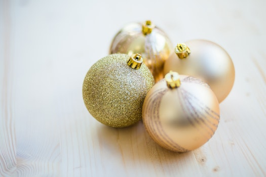 4 Christmas Baubles on Beige Wooden Flooring