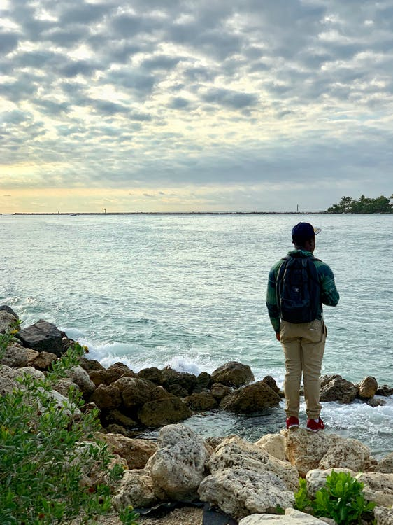 Man Standing on Rocks by the Water
