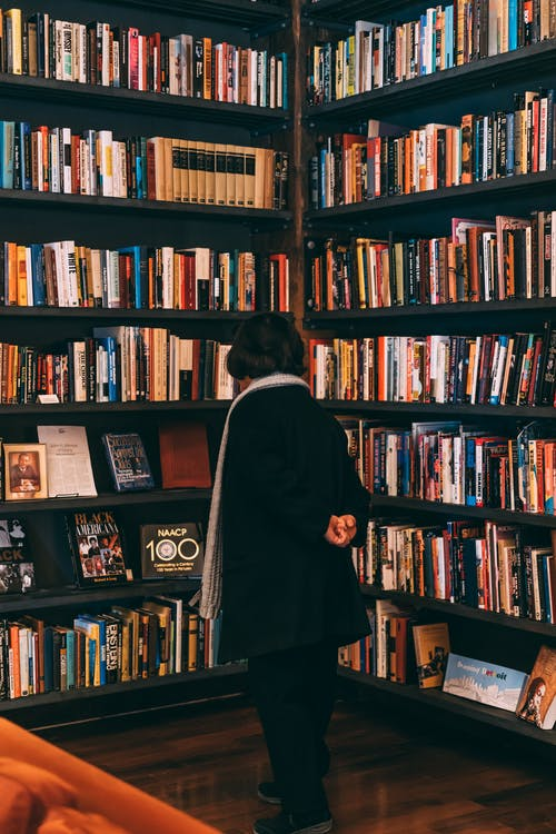 Woman Standing Beside Bookcase