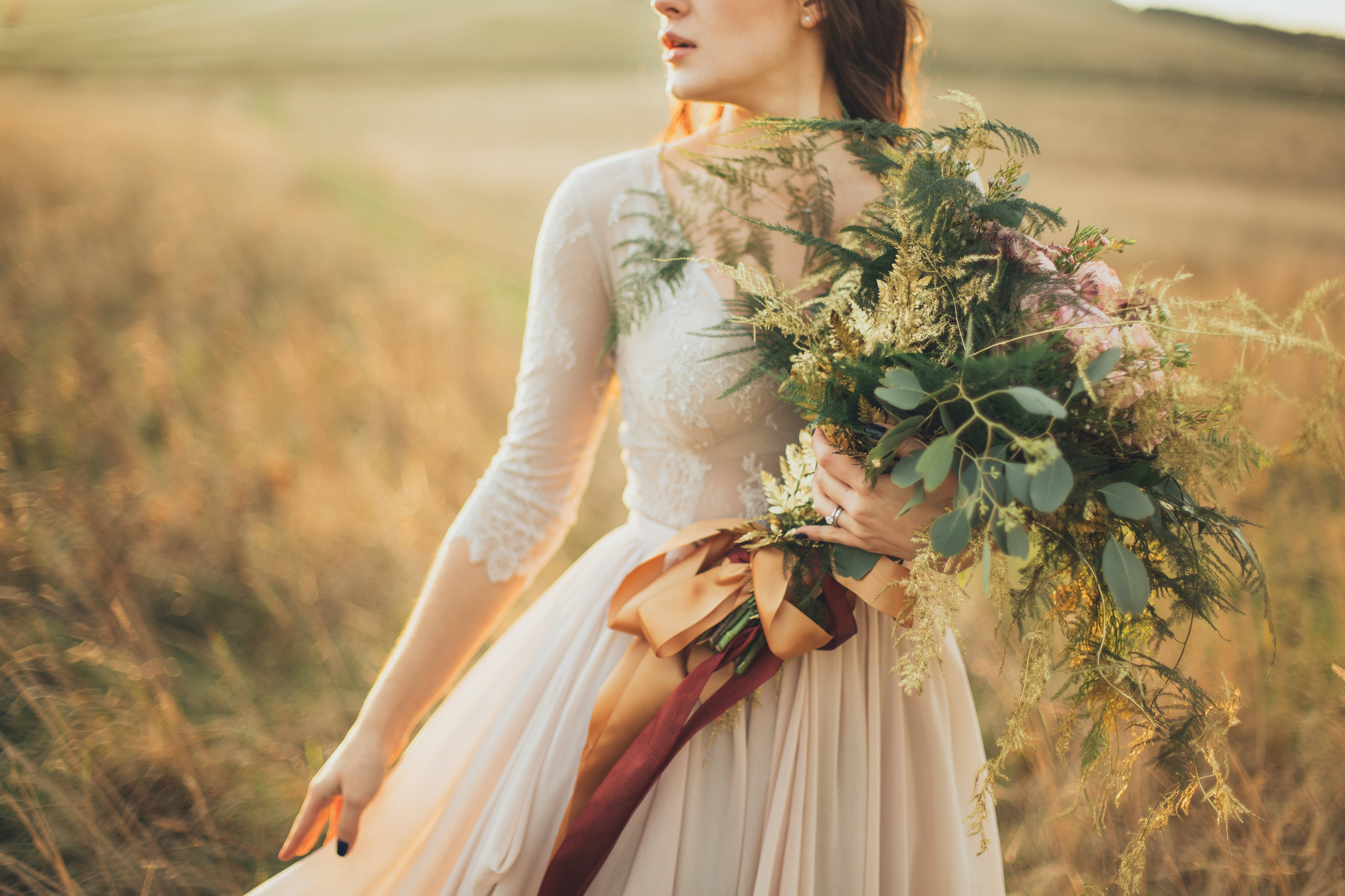 Woman Holding Bouquet In The Middle Of The Field