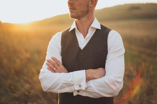 Man Wearing White Dress Shirt With Black Vest Standing on Grass Field during Sunset