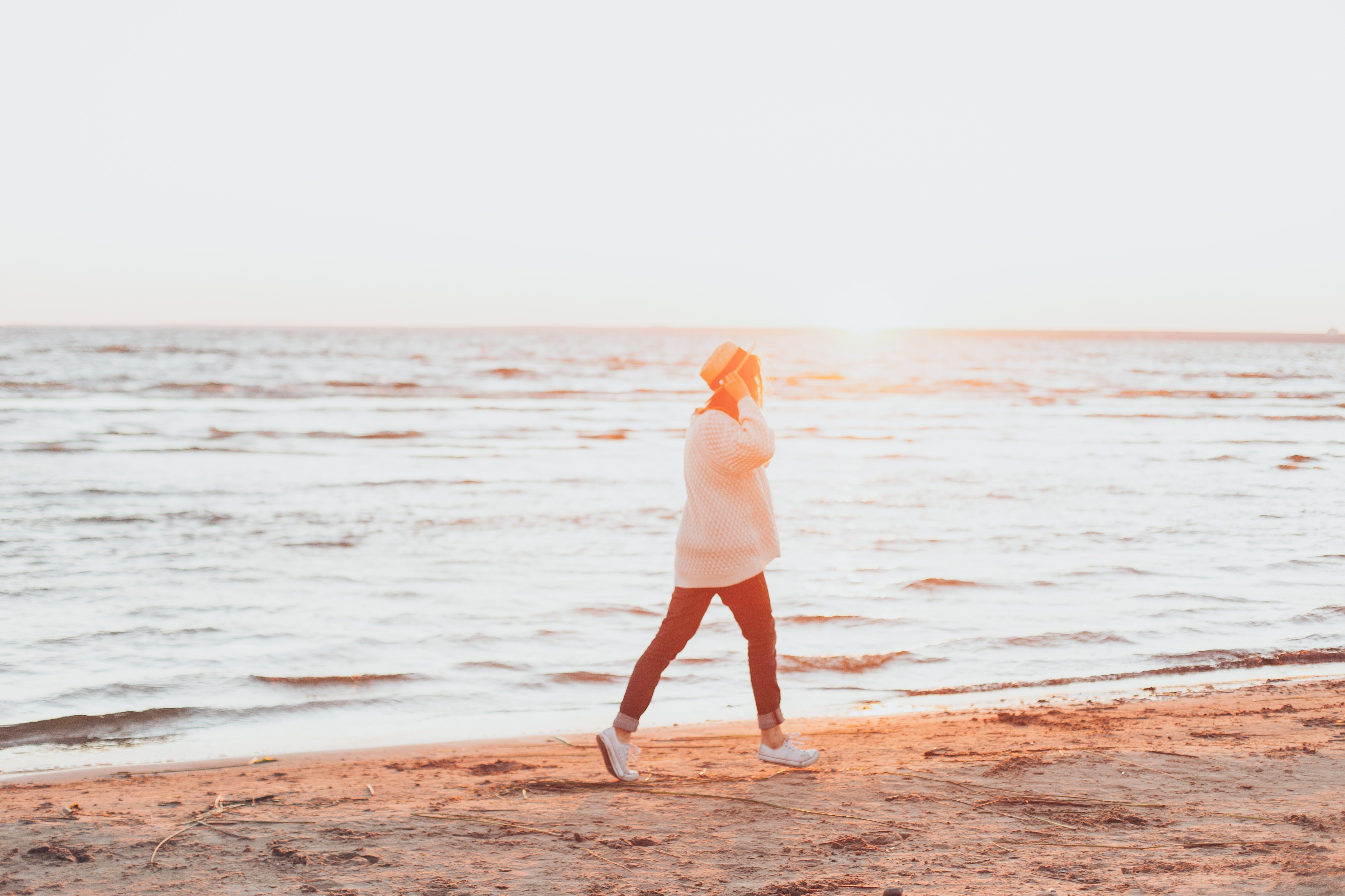 Photo of Person Walking On Seashore