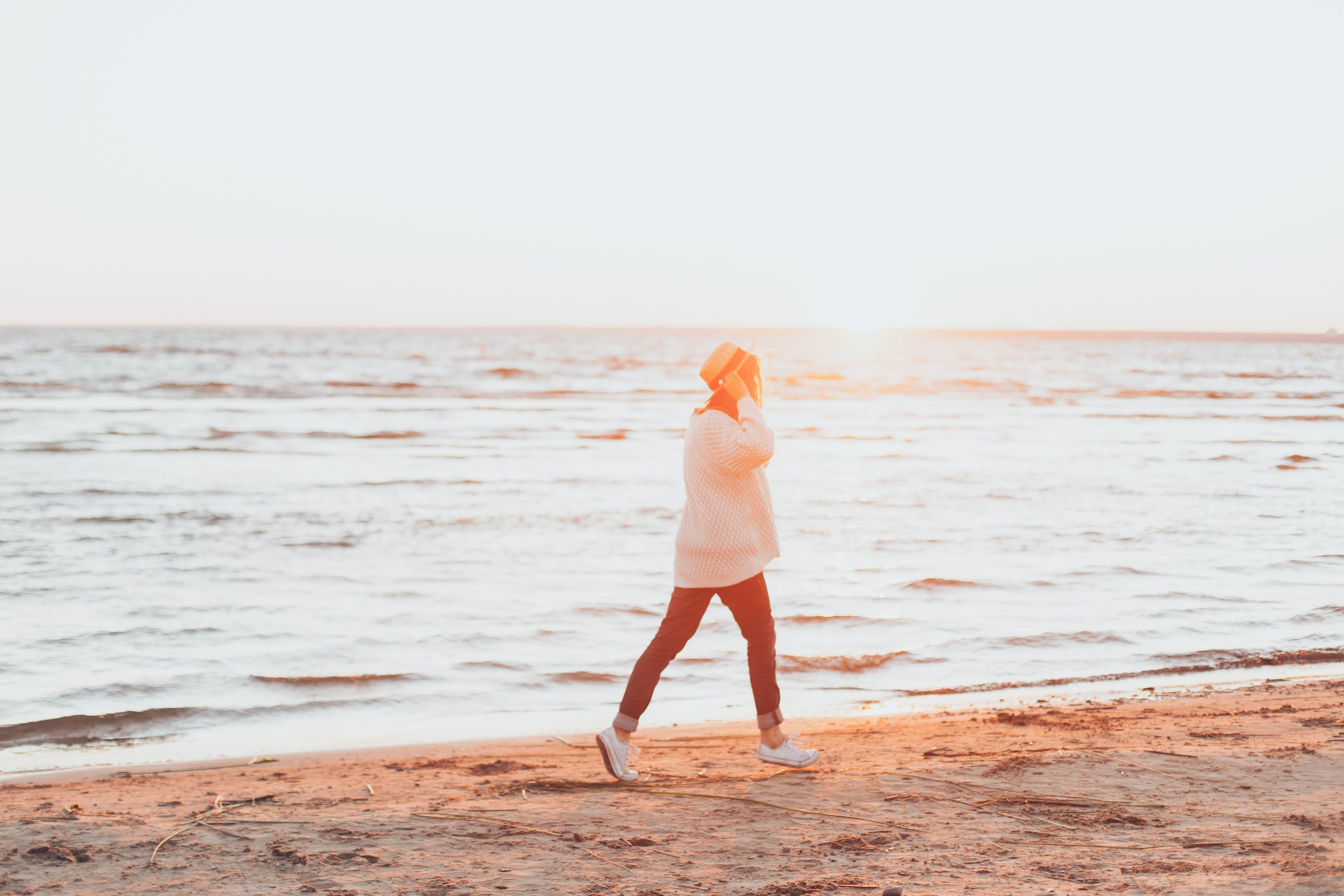 Photo of Person Walking On Seashore