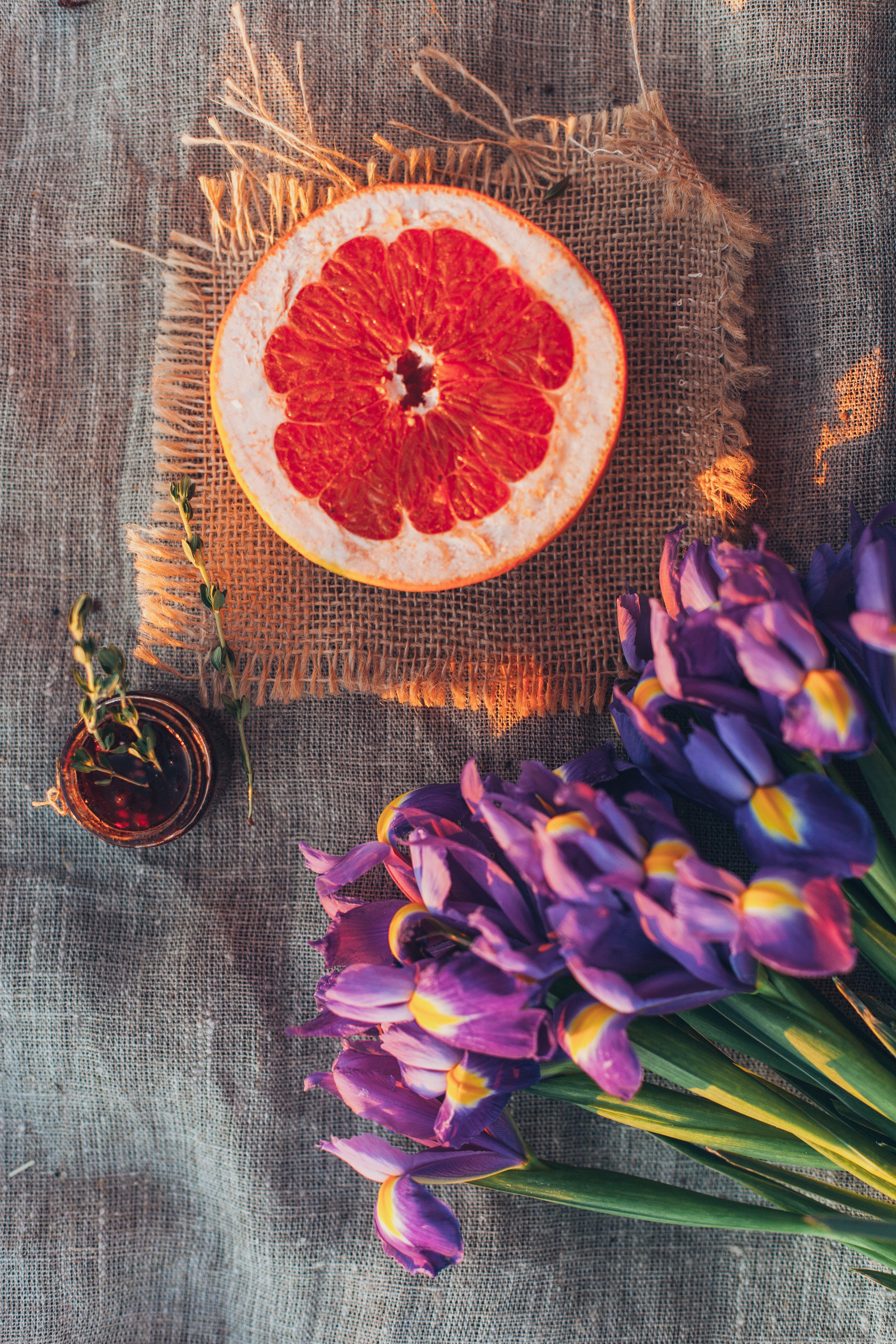 Top View Photo of Sliced Orange Near Flowers