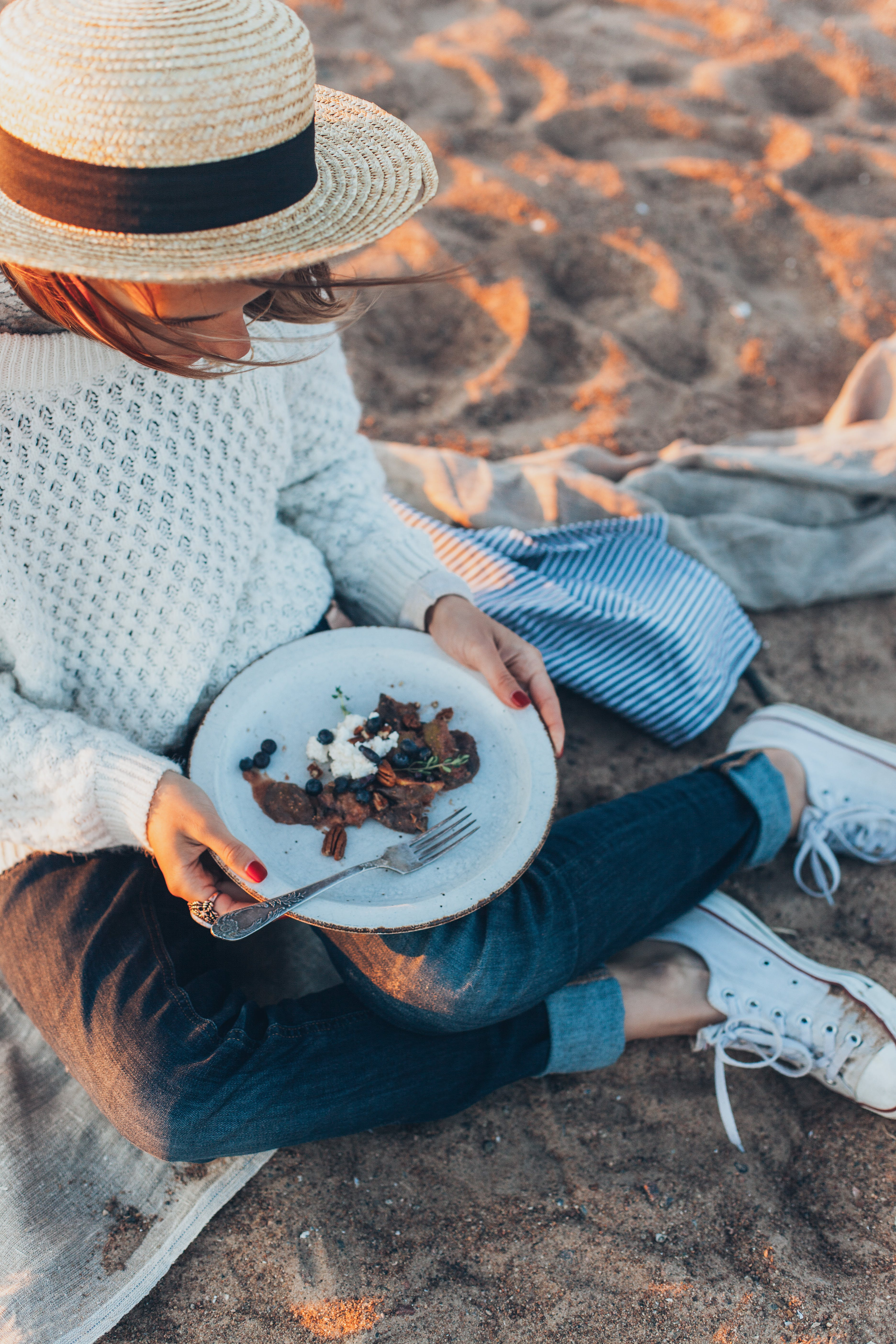 Woman Holding Plate While Sitting on Sand