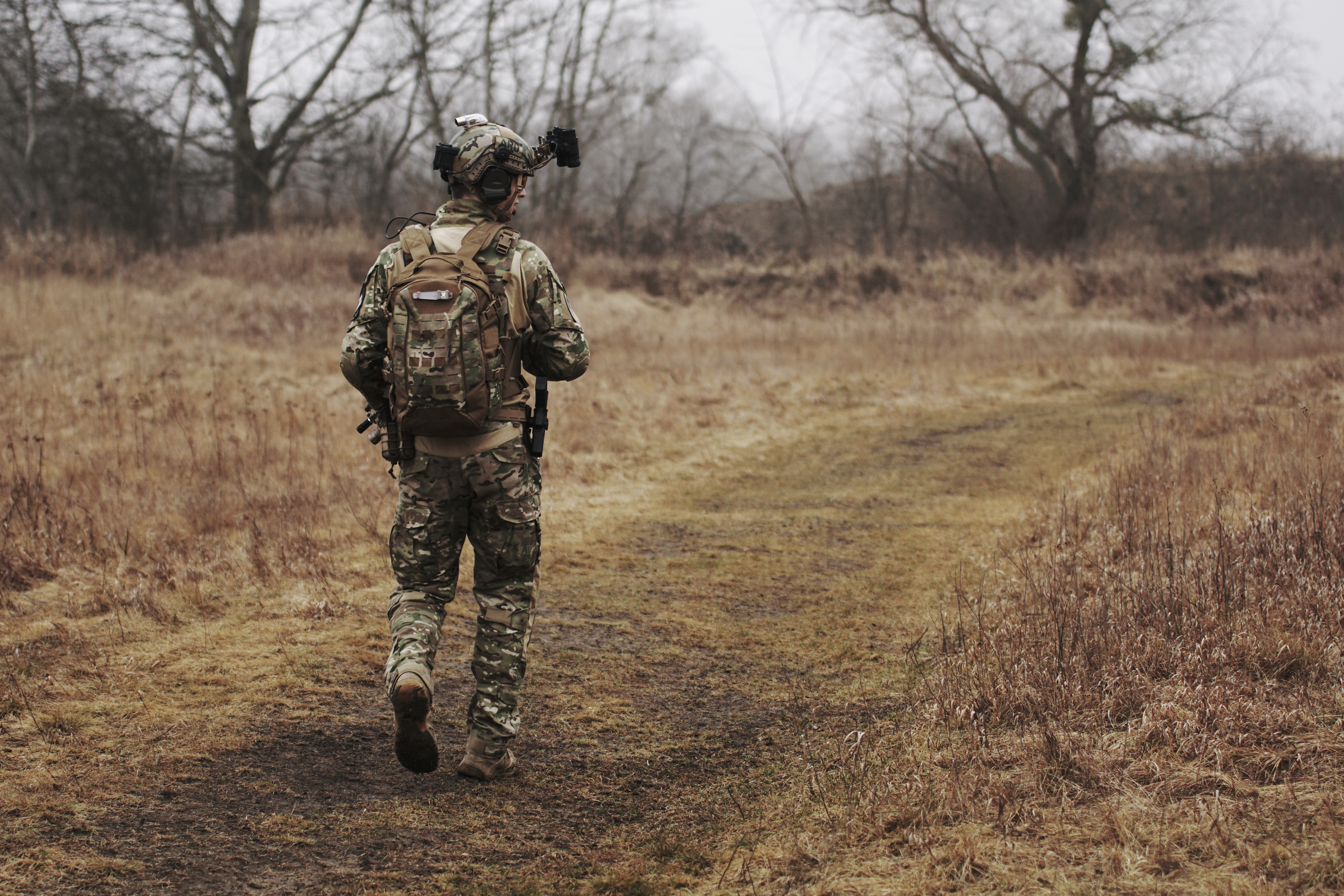 Man Wearing Military Uniform and Walking through Woods