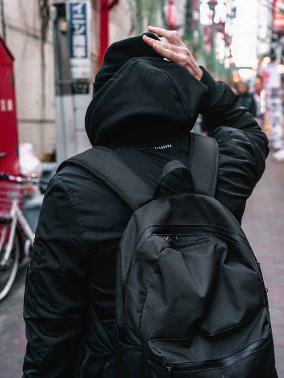 身穿黑色連帽衫站在大街上的人