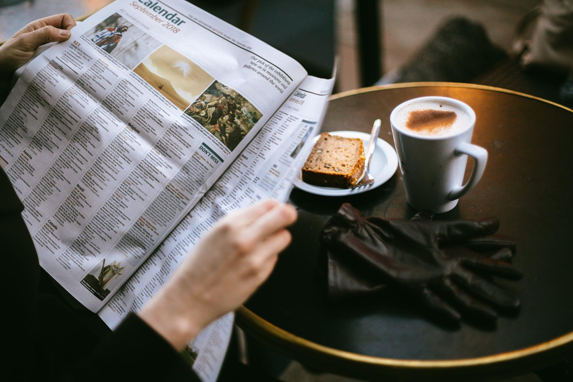 Manos de mujer leyendo el periódico junto a una mesa con café y un bizcocho
