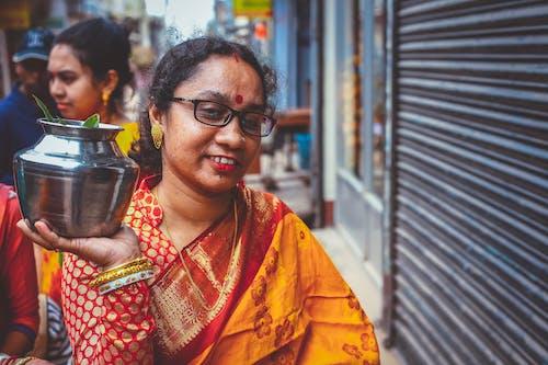 Woman in Orange and Yellow Sari Holding Black Ceramic Mug