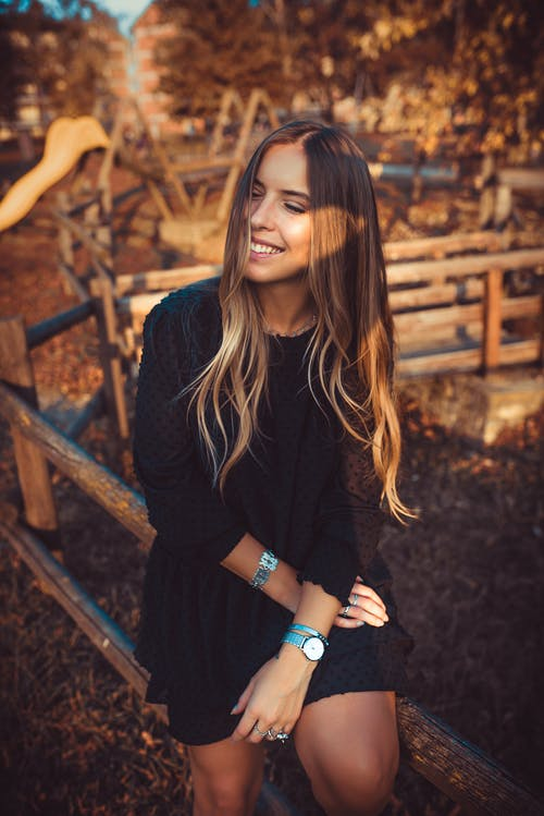 Smiling Woman Wearing Black Crew-neck Long Sleeved Midi Dress Sitting on Brown Wooden Rail