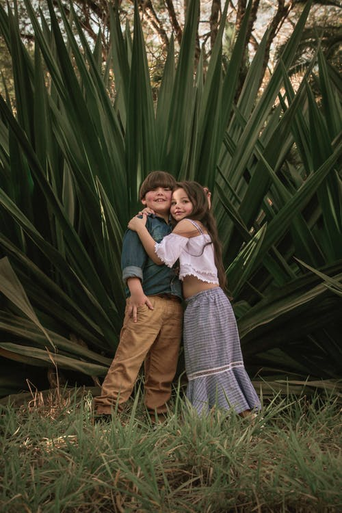 Boy And Girl Standing Near Green Leafed Plants