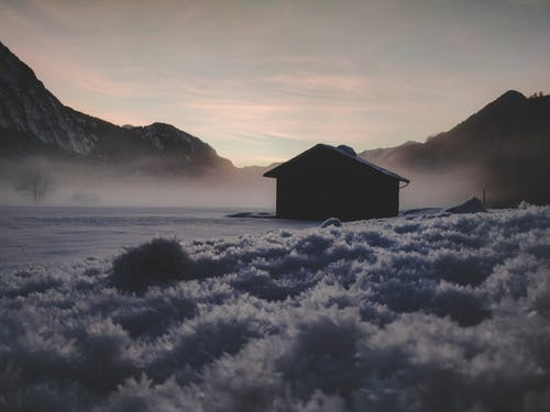 Silhouette of House Near Mountains