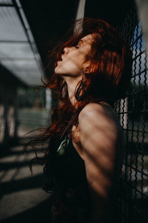 Photo of Woman Leaning on Chain-link Fence With Her Chin Up